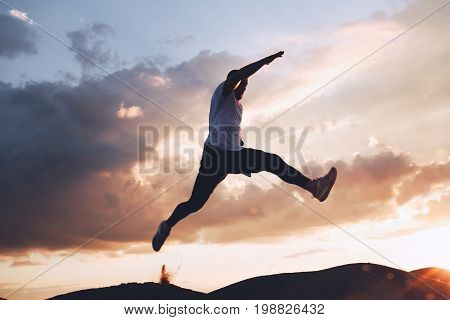Sportsman is extreme in a jump on background of beautiful clouds at sunset. Parkour freerun. Intentional dark colors