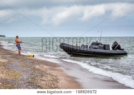 Man pulling a rope to keep his boat on shore. Gotska sandon Sweden - August 2 2017: Side view of a caucasian man on an island beach in the Baltic sea pulling a rope to stop his black speed boat from drifting away.