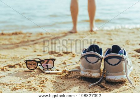 sunglasses with snickers on the beach, man stands on background in sunny summer day