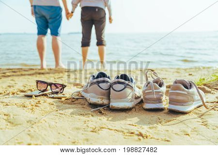 sunglasses with snickers on the beach, couple on background in sunny summer day