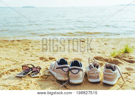 sunglasses with snickers on the beach, water on background in sunny summer day