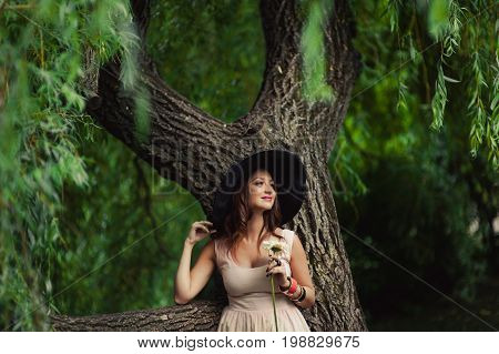 A Girl In A Hat With Wide Brim Near The Willow