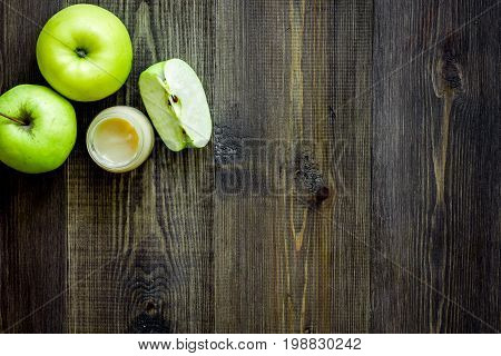 Apple puree for baby on dark wooden background top view.