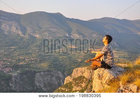 Young man sits on a cliff edge on the top of mountain and meditate. Dangerous Place. Adrenaline. Hiker on the top