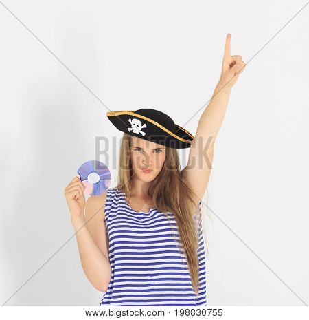Nice young woman with pirate cd or dvd disk and hat with skull and crossbones. Hand up and attention sign with her finger. Concept of software piracy and copyrighting
