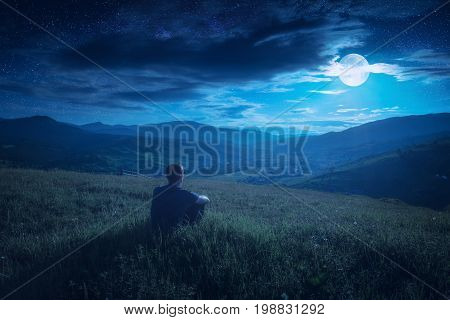 Human Sitting On A Hill In And Enjoy Moon Rising
