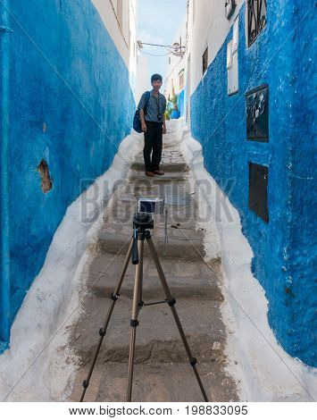 Udayas Rabat Morocco - May 06 2017: Asian tourist taking a photo of himself using a tripod in a narrow alley in the Kasbah of Udayas Rabat Morocco May 2017.