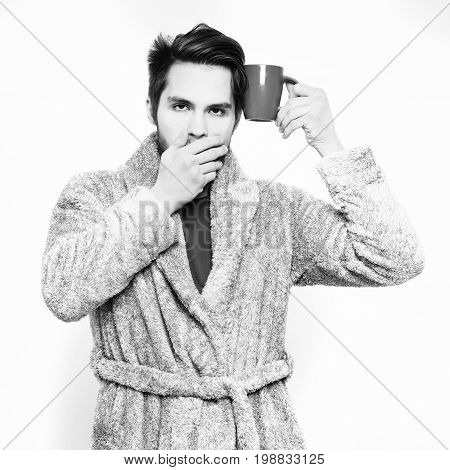 Handsome Bearded Yawning Sleepy Man With Cup In Terry Bathrobe