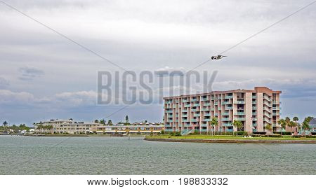 Water front condominium building on a bay with a seagull flying by on an overcast day. Crystal Beach, Florida, USA