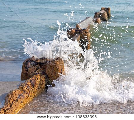 Stone wave breaker on the shore of the ocean with a wave breaking on it, Madeira Beach, Florida, USA