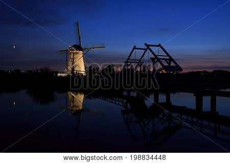 An illuminated windmill and a drawbridge with reflection in the still water of the canal during Blue Hour at sunset in Kinderdijk in the Netherlands.