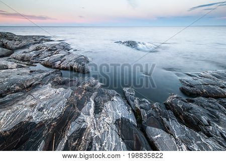 Morning tranquil landscape of stony coast with gray rocks and calm water under blue sky in twilight in early morning beautiful calm natural background.