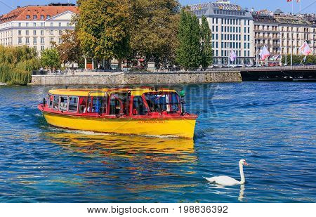 Geneva, Switzerland - 24 September, 2016: a yellow boat on the Rhone river, buildings along the river in the city of Geneva. The city of Geneva is the capital of the Republic and canton of Geneva, being the second most populous city in Switzerland.
