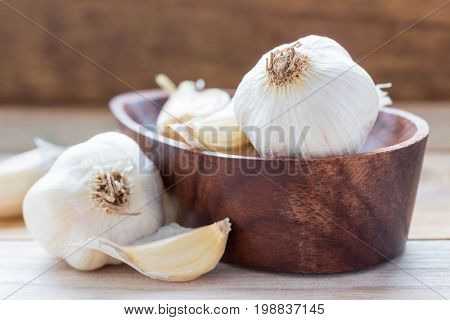 Garlic Cloves and Garlic Bulb in vintage wooden bowl.Garlic is a Thai herb and is a spice. Usually put in many kinds of food.