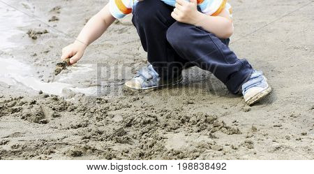Children's outdoor play.A child squatting near a large puddle. Child is digging with a stick a trickle.