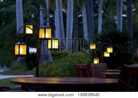 Romantic lanterns by wooden tables at a trpical sunset.