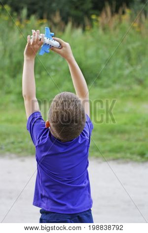 Children's outdoor play. A child plays with an airplane. The boy raised his hand and launches into the sky a toy plane.