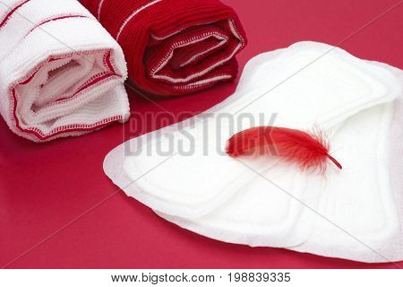 Menstruation sanitary hygiene protection. Hygiene concept photo. Bath terry towels red feather on the heap of menstrual woman pads for blood period. Woman critical days and menstruation cycle