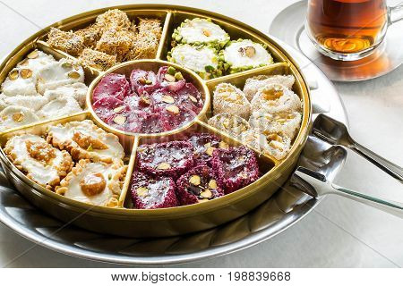 Eastern sweets. Assorted traditional Turkish delight (Rahat lokum) on gray stone background. Turkish delight with different nuts and coconut shavings tea in glass (armud) and tongs for sweets