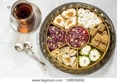 Eastern sweets. Assorted traditional Turkish delight (Rahat lokum) on gray stone background. Turkish delight with different nuts and coconut shavings tea in glass (armud) and spoons. Top view