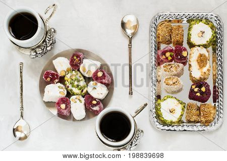 Eastern sweets. Assorted traditional Turkish delight (Rahat lokum) on gray stone background. Turkish delight with different nuts and coconut shavings coffee in cups and spoons. Top view poster