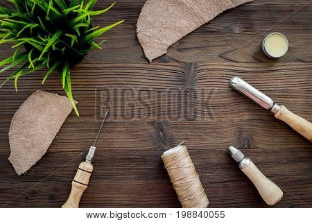 Leather craft. Tanner's tools on dark wooden table background top view.
