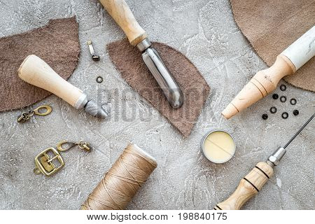 Leather crafting tools on grey stone background top view.