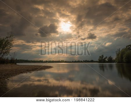 Long exposure at the lake with natural shore at sundown sunrays shining through the clouds