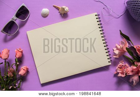 Flat lay with white paper and sunglasses on violet background. Romantic pink rose flower bouquet. White paper notepad with text place. Feminine banner template with text place. Artistic sketch mockup