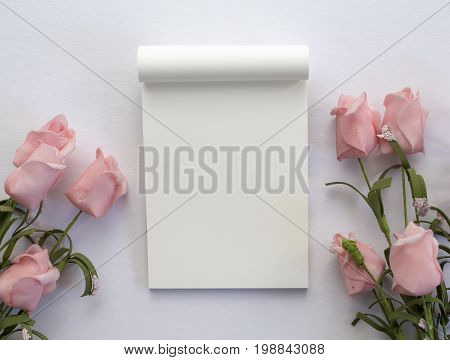 Flat lay with notepad and roses on white background. Romantic banner template with text place. Wedding backdrop with roses and blank white page notepad. Pastel pink flowers on white table top view
