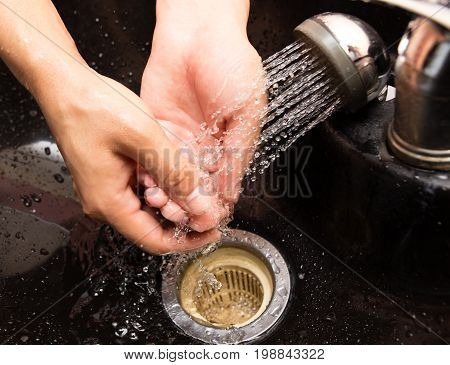The man washes his hands in the sink .