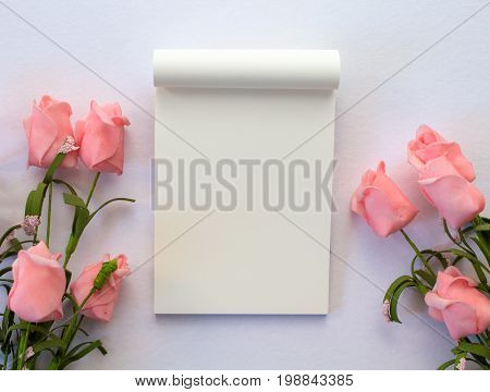 Flat lay with notepad and roses on white background. Romantic banner template with text place. Wedding backdrop with roses and blank white page notepad. Gentle pink flowers on white table top view