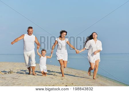 A cheerful family runs along the beach in the summer