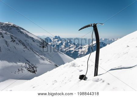 Ice ax in the snow against the background of snow-covered rocks. The concept of extreme mountain sports