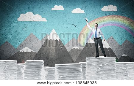 Businessman keeping hand with book up while standing on pile of paper documents with drawn landscape on background. Mixed media.