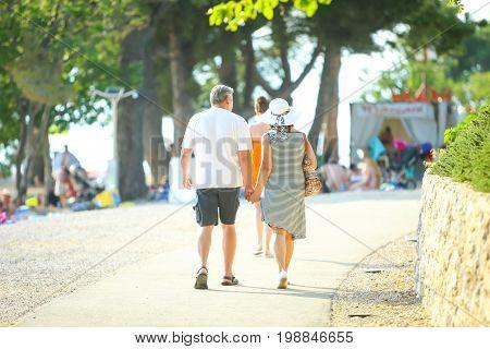 Senior couple walking on the beach and holding hands in Njivice island of Krk Croatia.