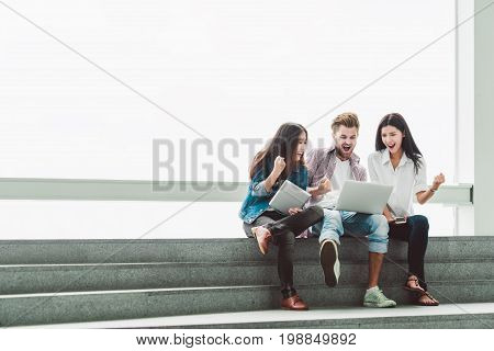 Multi-ethnic group of young college students or freelance coworkers celebrate together with laptop and tablet. Creative team or business colleague at modern office. Startup teamwork success project concept