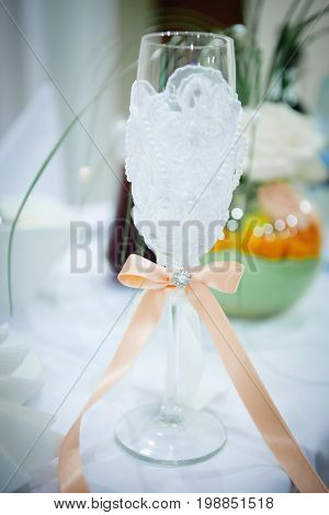 Wedding glass with champagne decorated with lace and satin bow