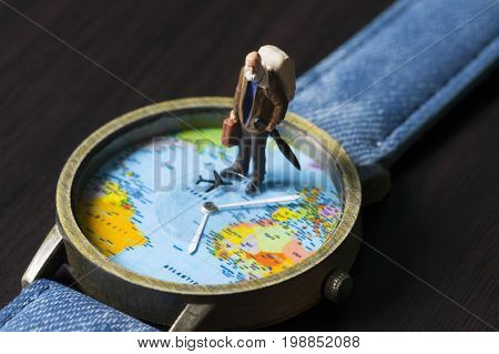 Old man on watches with world map. World travel photo banner. Senior traveler figurine. Retired backpacker travel. World time zones. Travelling around world concept. Senior age travel. Time of life
