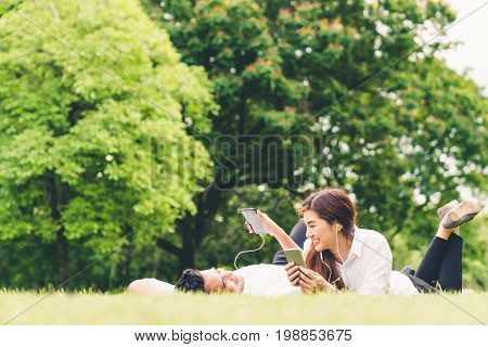 Young Asian lovely couple or college students listening to music together in the garden with copy space. Leisure activity Love relationship wedding or relaxing casual lifestyle concept