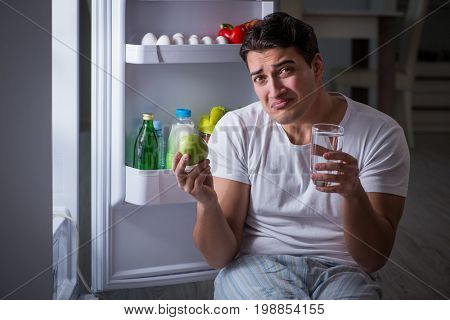 Man at the fridge eating at night