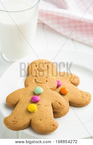 Sweet gingerbread men and glass of milk. Xmas gingerbread on white table.