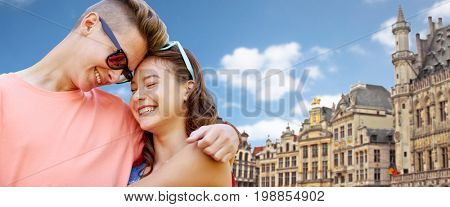 love, travel, tourism and people concept - happy smiling teenage couple hugging over grand place in brussels city background