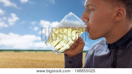 people, drinks, alcohol and leisure concept - close up of young man drinking beer from glass mug over cereal field and blue sky background