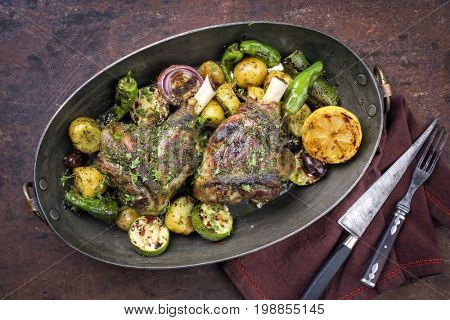 Barbecue leg of lamb with vegetable and potatoes as top view in a casserole