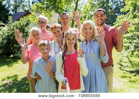 generation and people concept - happy family taking picture with selfie stick in summer garden