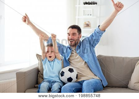 family, entertainment, sport and people concept - happy father and little son with ball watching football or soccer game tv at home