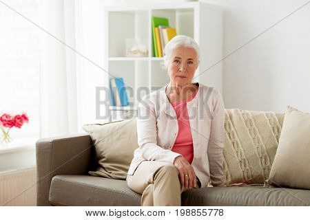 old age and people concept - senior woman sitting on sofa at home