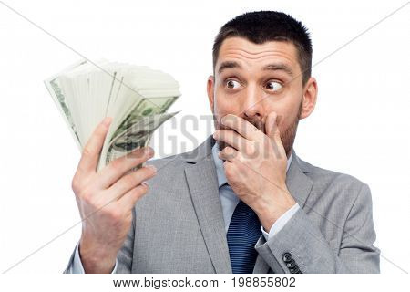 business, people and finances concept - astonished businessman with bundle of american dollar cash money