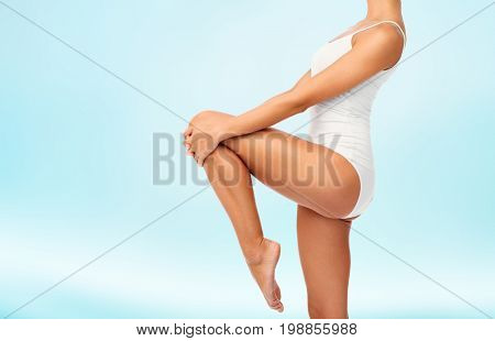 beauty, people and bodycare concept - close up of beautiful young woman in white underwear over blue background
